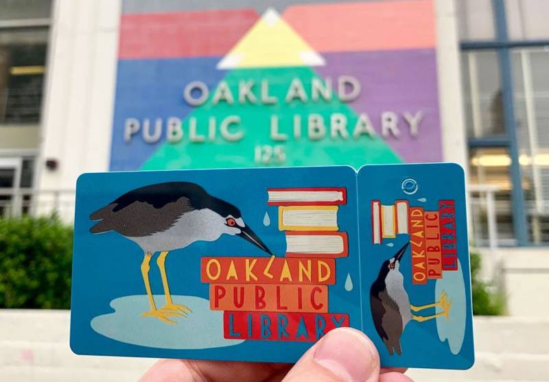 Someone holding a colorful Oakland Public Library card that has the image of a grey heron and a stack of books on it.