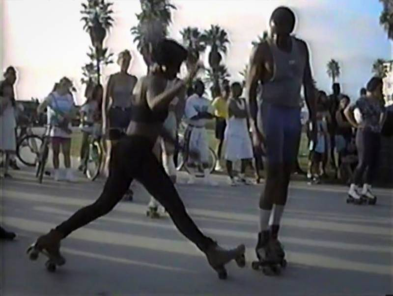 Female roller skater about to do a split at Venice Beach, CA. Still from a homemade video from 1990s.