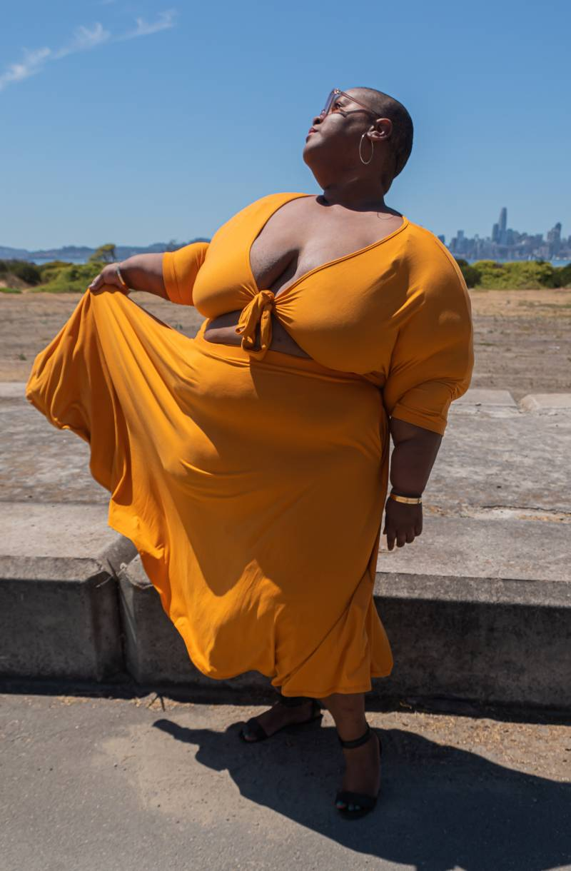 Brena Jean in matching yellow top and skirt. She stares up towards the sun, soaking up its rays while lifting a corner of her skirt.