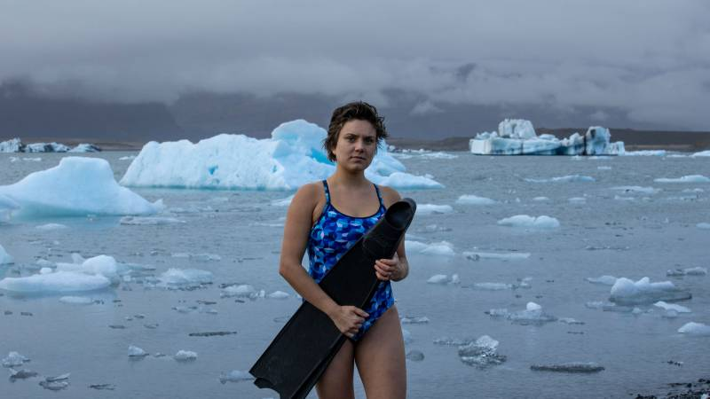 A young white woman with short brown hair wears a blue patterned one-piece bathing suit and holds large black flippers across her body. Behind her ice floats in water.