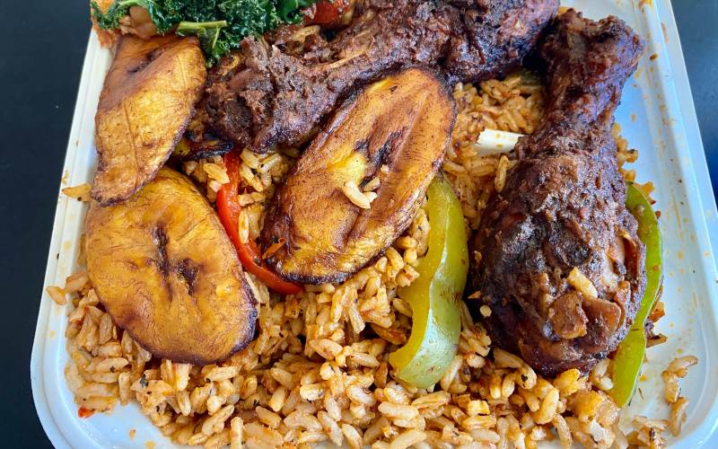 Takeout container of jollof rice topped with plantains and baked chicken