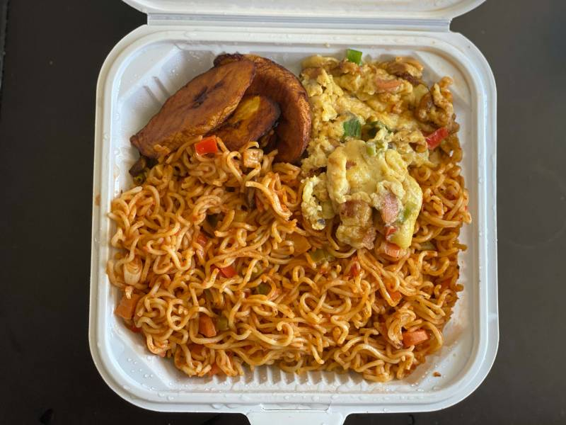 Overhead view of jollof Indomie: Indomie instant noodles tossed with vegetables and topped with plantains and scrambled egg