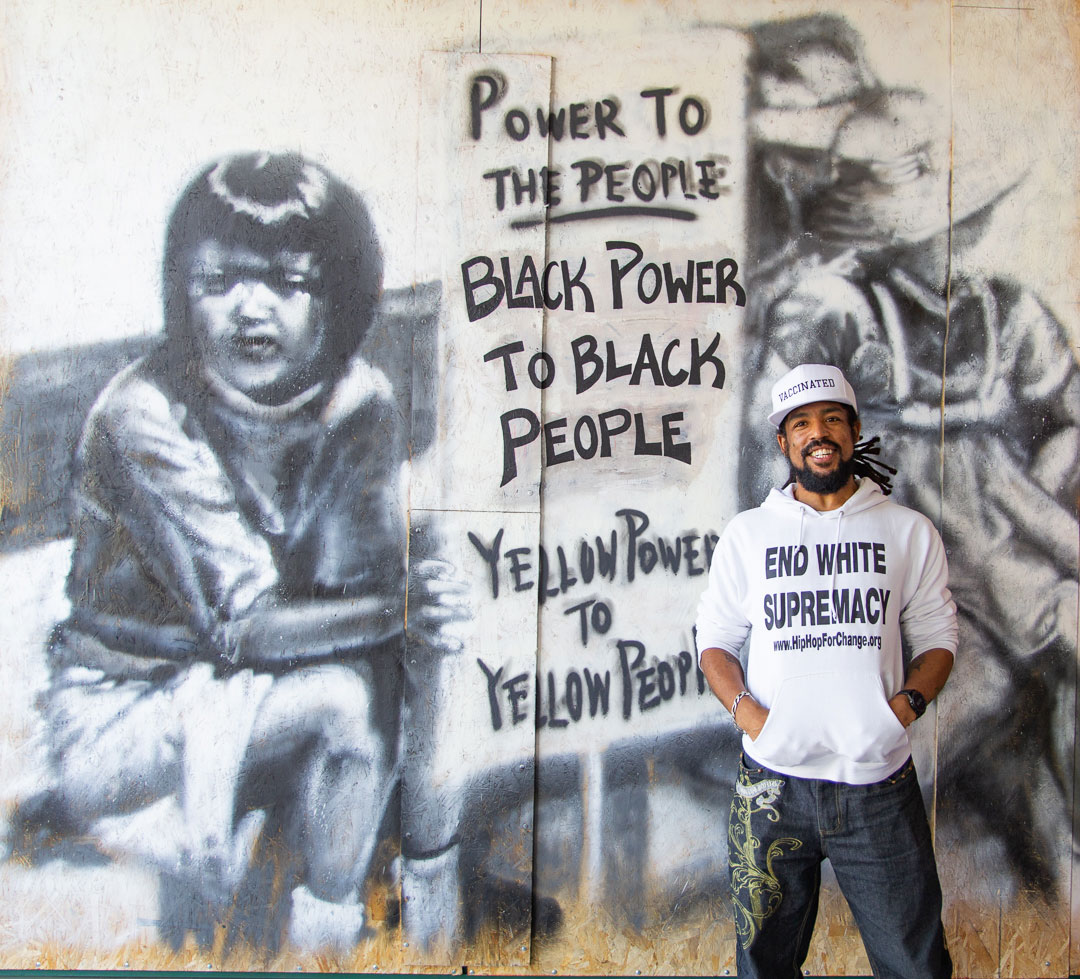 Khafre Jay at a mural he recently restored in Oakland's Chinatown.