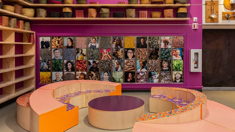 A community gathering area, colorfully decorated with curved banquette seating and a photo collage on the wall.