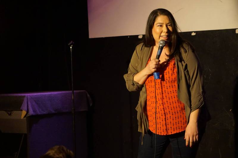 Standup Comedian Jackie Keliiaa holds a microphone on stage, she leans forward slightly, smiling out at the audience.