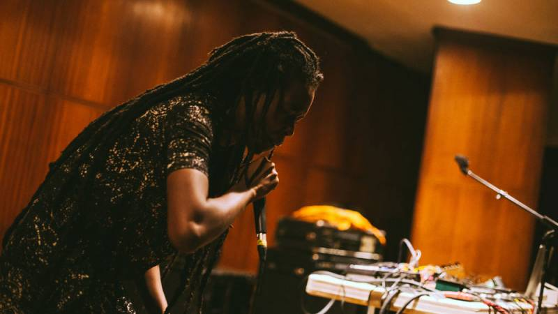 Moor Mother performs at a DJ table
