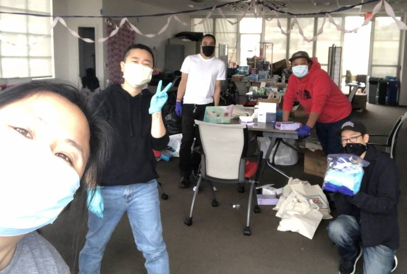 Volunteers with masks and gloves smile for a selfie.