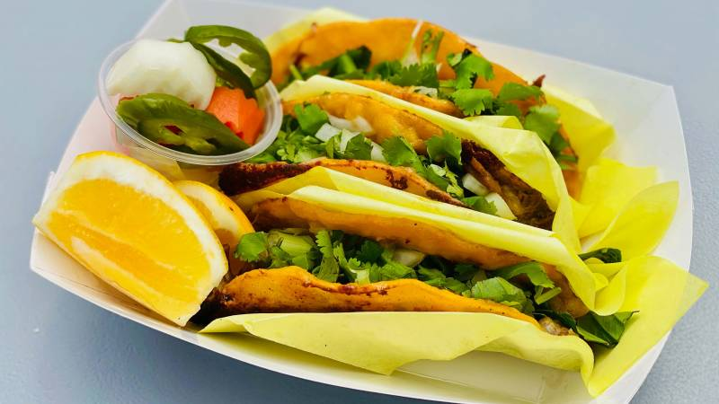 Three Vietnamese tacos in a cardboard sleeve.