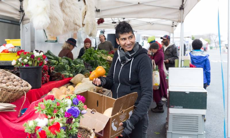 Chef Preeti Mistry browses the produce at a farmers market stall