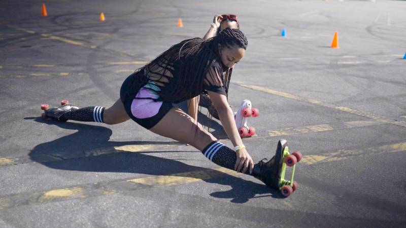 "Roller skater Raqual ""Roxy"" Young doing splits on the pavement"