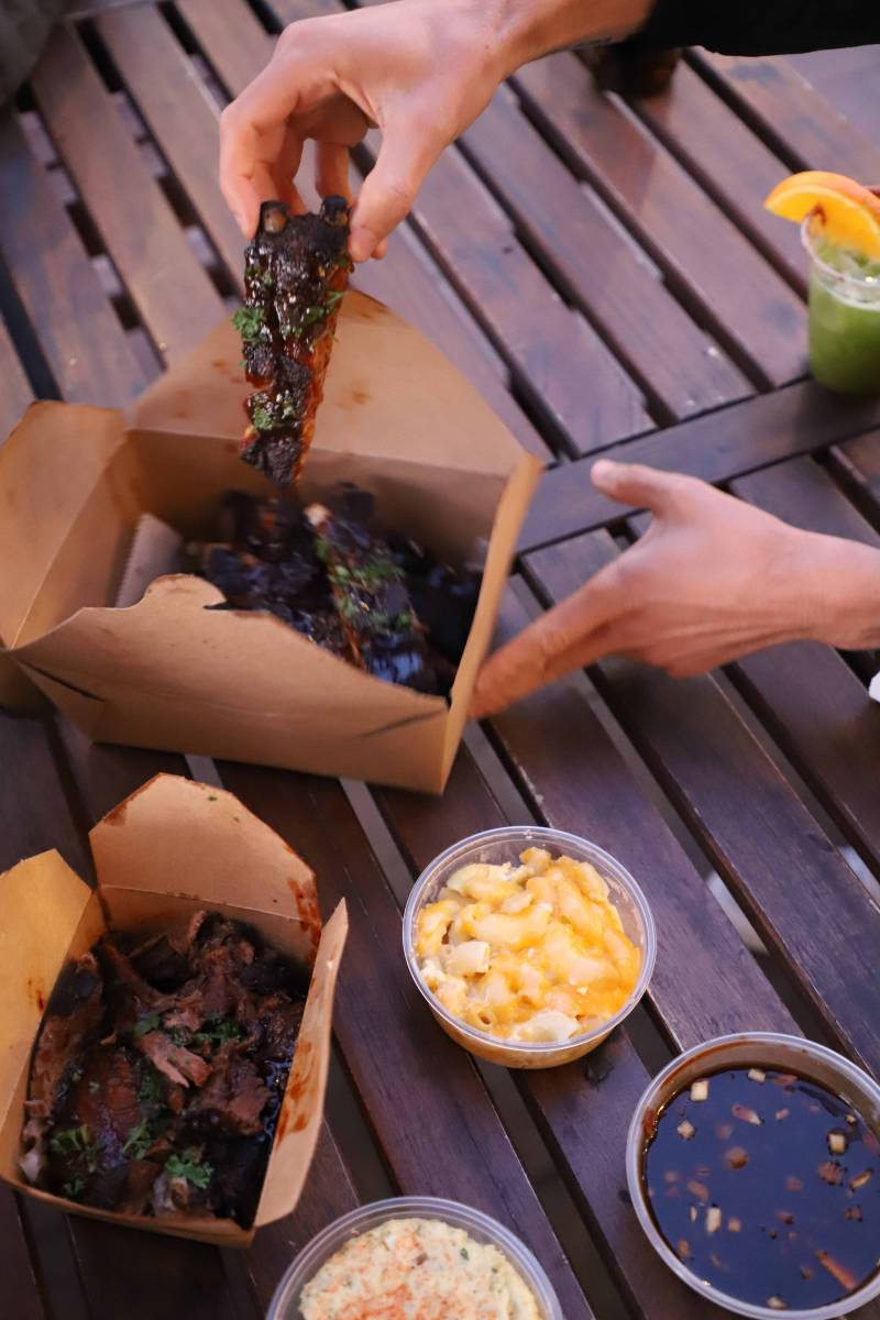 Takeout containers of barbecue and mac and cheese on a picnic table.