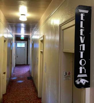 Upstairs at the Lan Mart: A long, narrow corridor of closed doors, beyond the elevator.