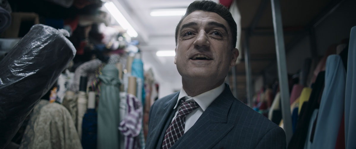A close-up view of the tailor character, dressed in a pristine three-piece suit with a checkered tie, behind him are bolts of fabric in many patterns and colors. He looks hopeful, as if about to say something.