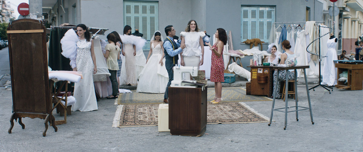 An outdoor scene of many women dressed in glamorous white wedding dresses, clustered around a tailor in a gray vest and pants fitting a smiling woman in a white peplum top. A woman in a midi-length patterned red dress stands across from the tailor with her arms out in a questioning pose.