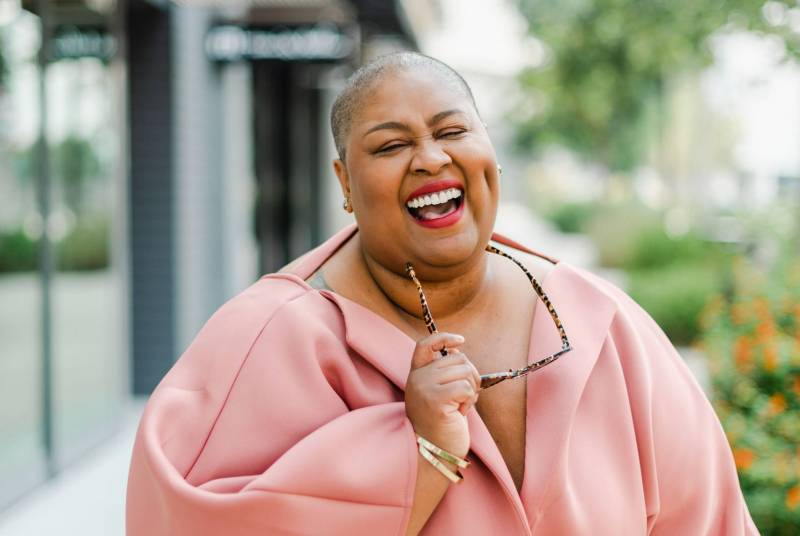 Brena Jean, advocate for those living with lipedema, takes a candid photo as she smiles and laughs while wearing a peach colored outfit and holding her glasses.