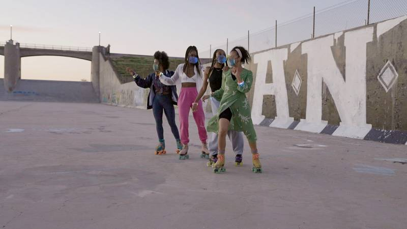 Four roller skaters posing together at dusk at the Sepulveda Dam in Los Angeles, CA