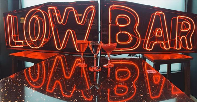 """Three cocktails glow red in front of a neon sign that reads """"Low Bar."""""""