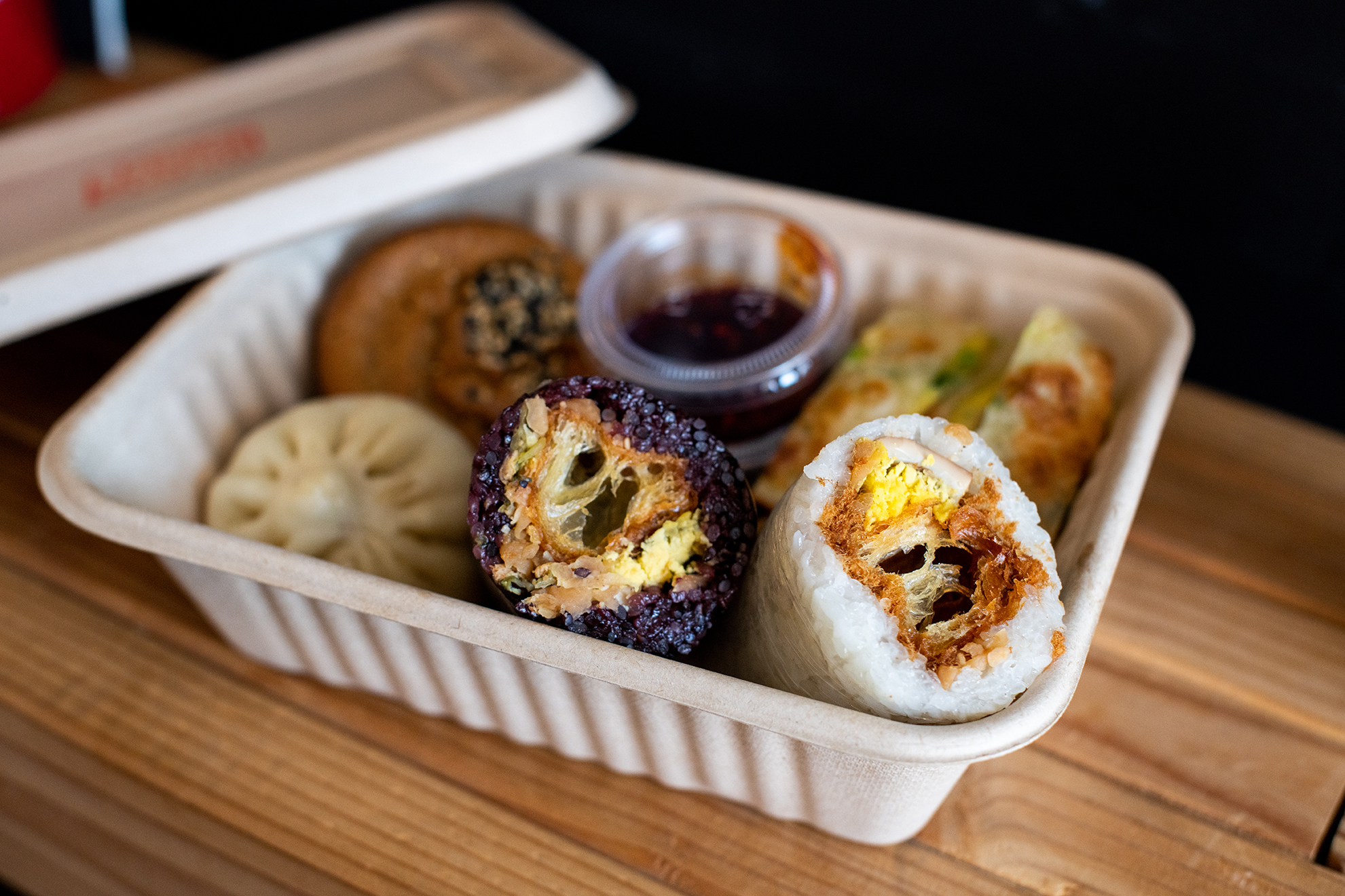 A takeout box with sticky rice rolls, scallion egg pancake, and other Taiwanese breakfast items from Taiwan Bento.