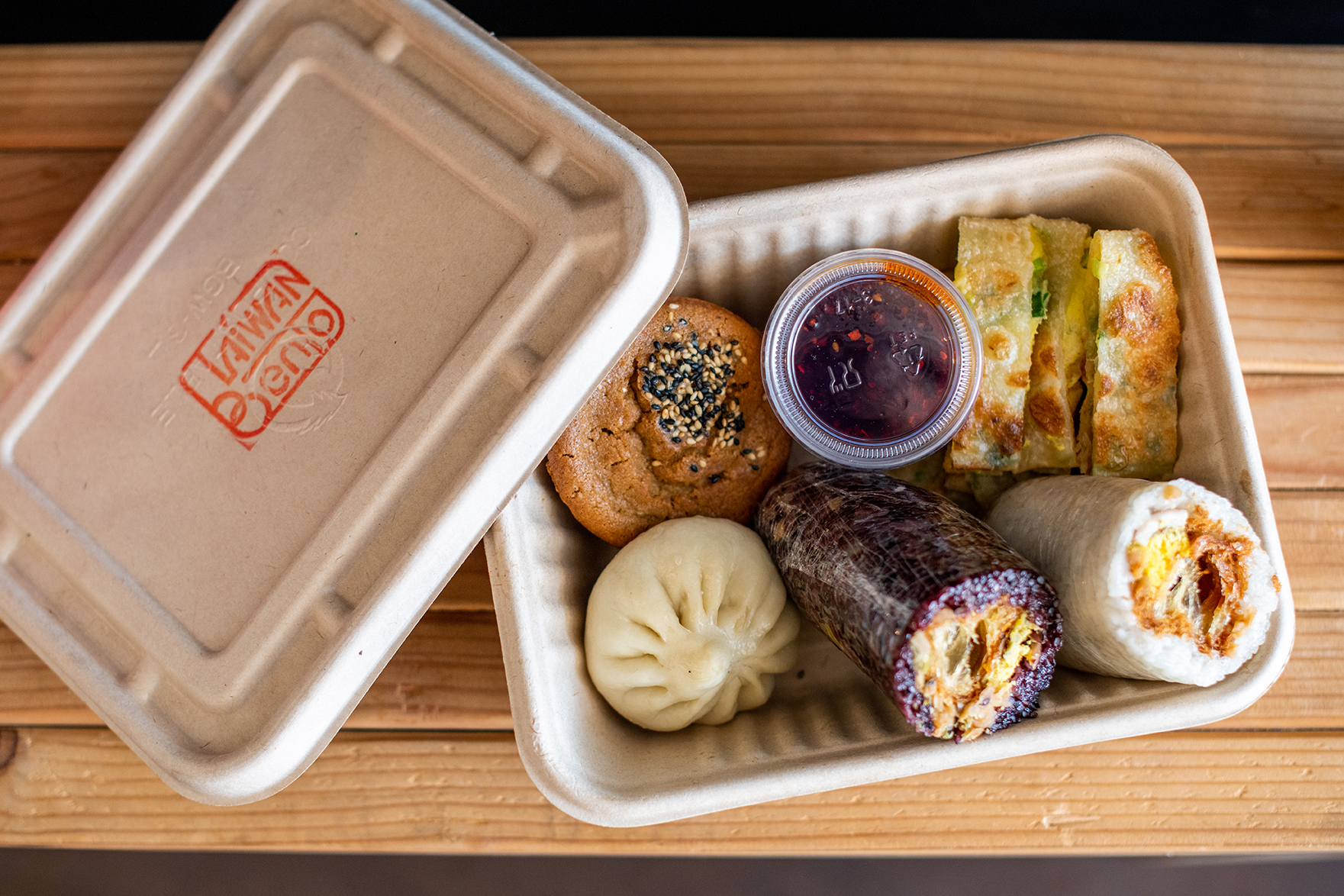 Overhead view of a takeout box with sticky rice rolls, scallion egg pancake, and other Taiwanese breakfast items from Taiwan Bento.