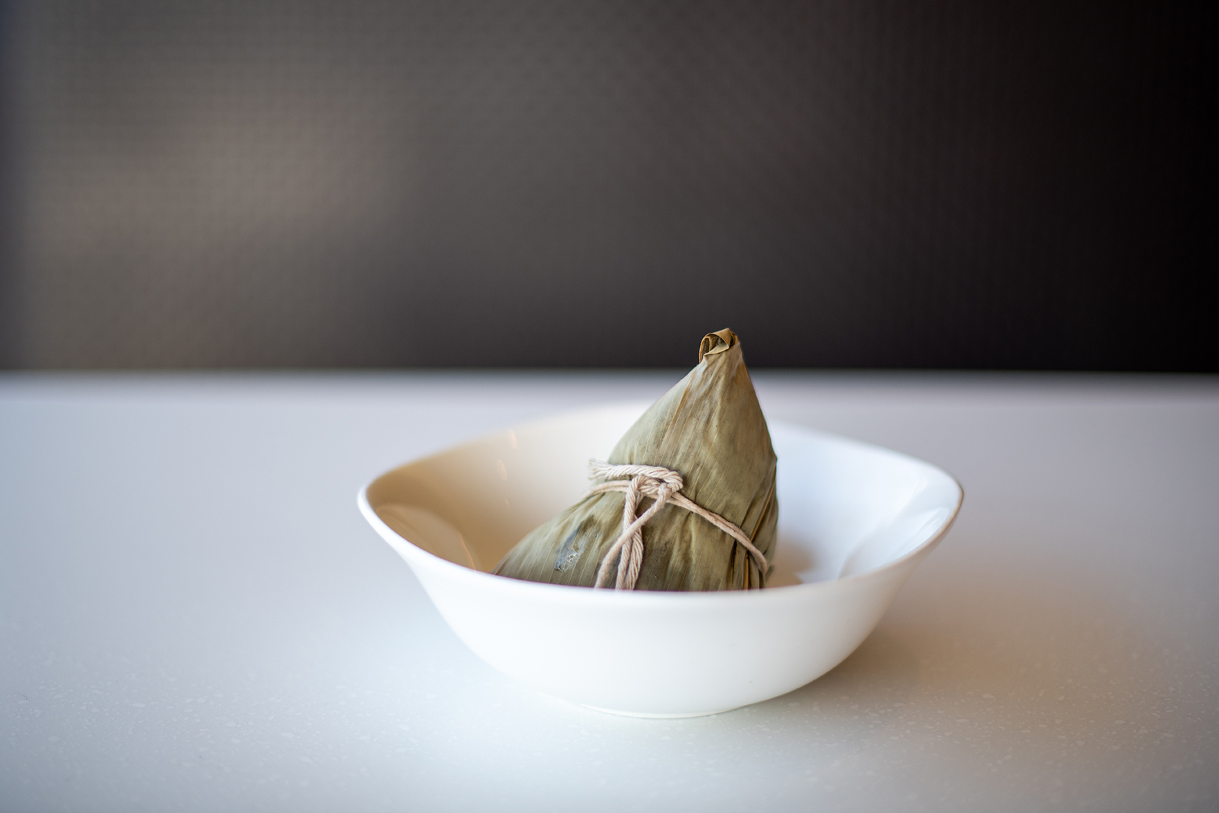 Taiwanese bah tsang (or leaf-wrapped rice dumpling) in a white bowl on a white countertop.
