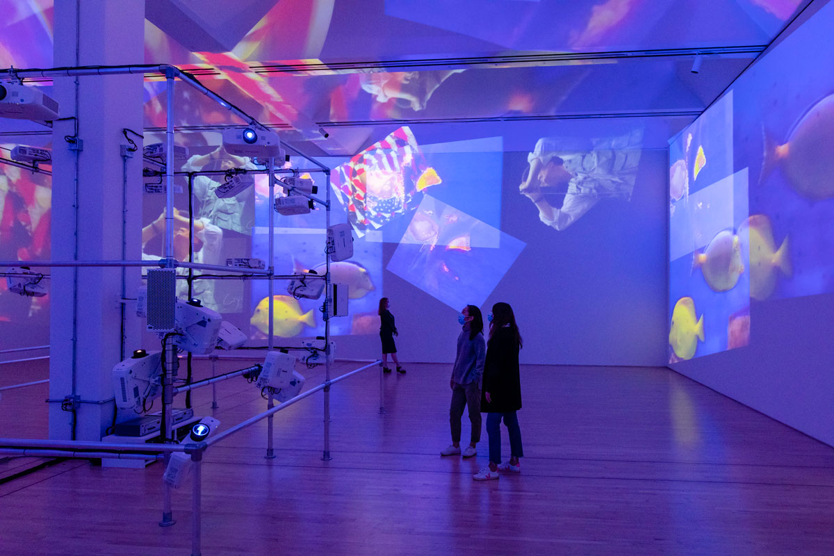In a large gallery filled with purple-blue light, multiple project images layer over the walls and ceiling as three people stand around watching.
