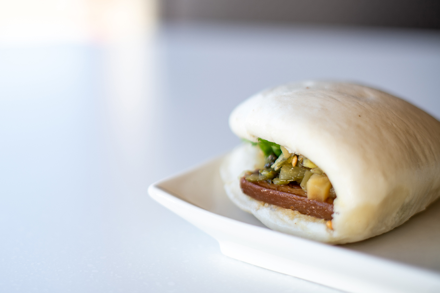 A traditional pork belly gua bao on a plate, on a white countertop.