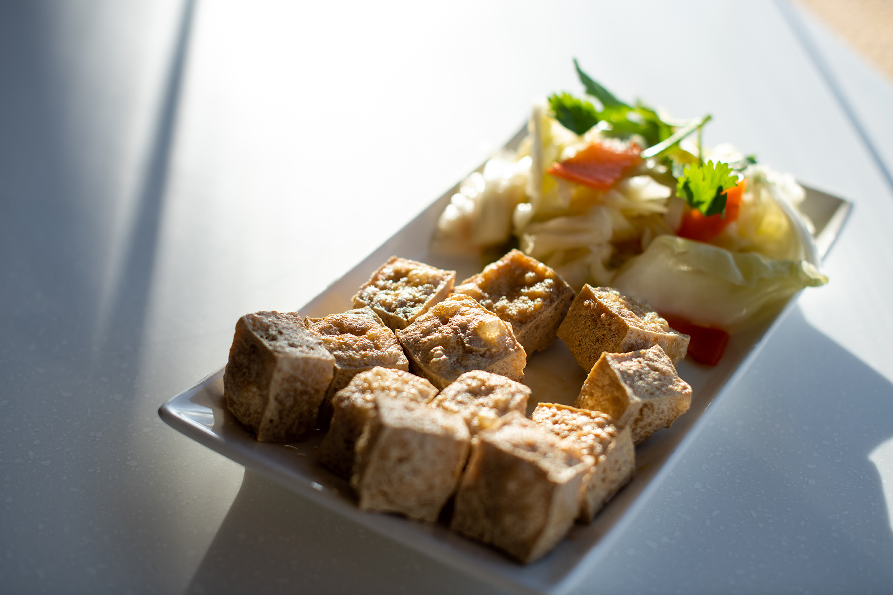 A plate of fried stinky tofu with a side of pickled cabbage on a white countertop.
