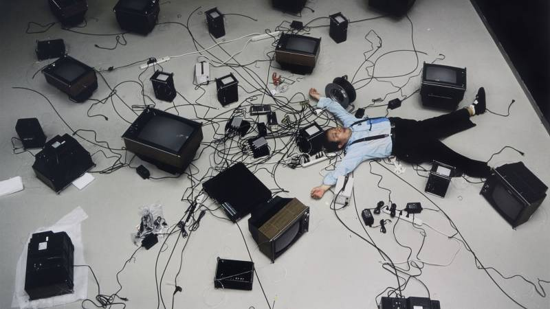 Seen from overhead, a man in light blue shirt and black pants lays spread-eagle surrounded by TVs and their cables