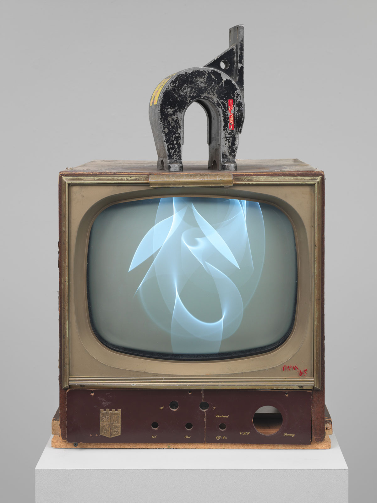 A U-shaped magnet on top of a CRT television creates an image of wavy, overlapping white lines on the dark gray screen.