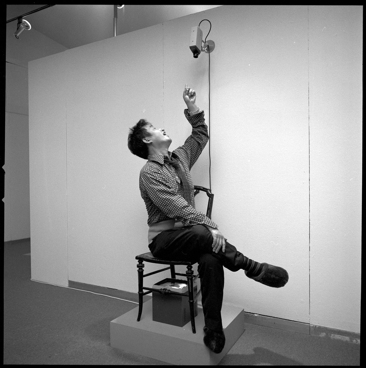 A black-and-white photo of a man sitting on a chair with one leg resting on the opposite knee. He looks up and points at a camera above his head.