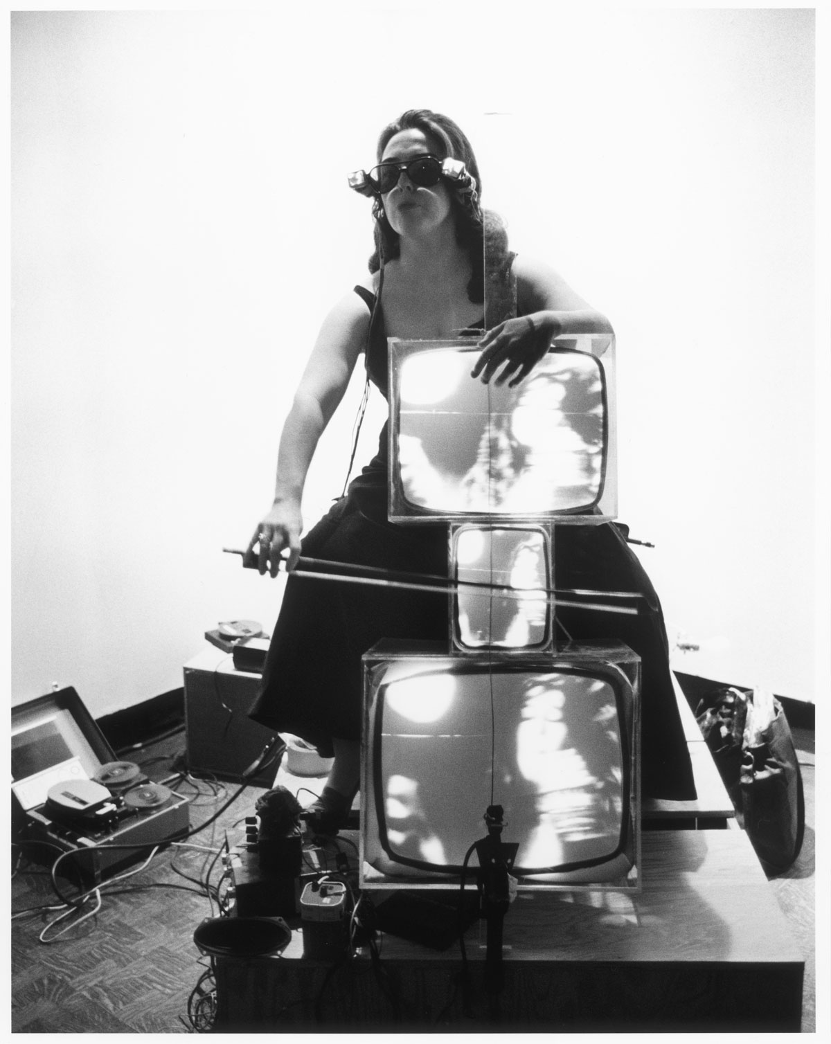 """In a black-and-white photo, a woman wearing glasses made from small TVs plays a """"cello"""" made from three TV monitors."""