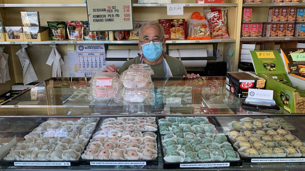 Mochi shop owner stands behind display case while wearing a face mask.