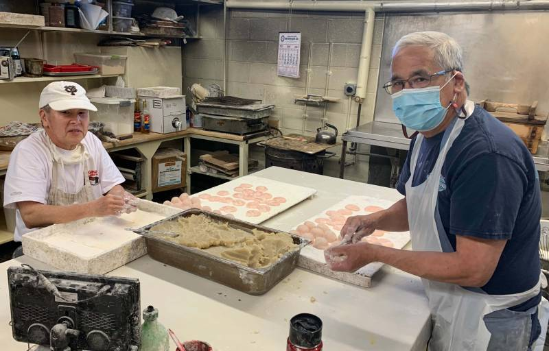 Benkyodo owners Ricky and Bobby Nakamura stuff pink mochi with white bean paste
