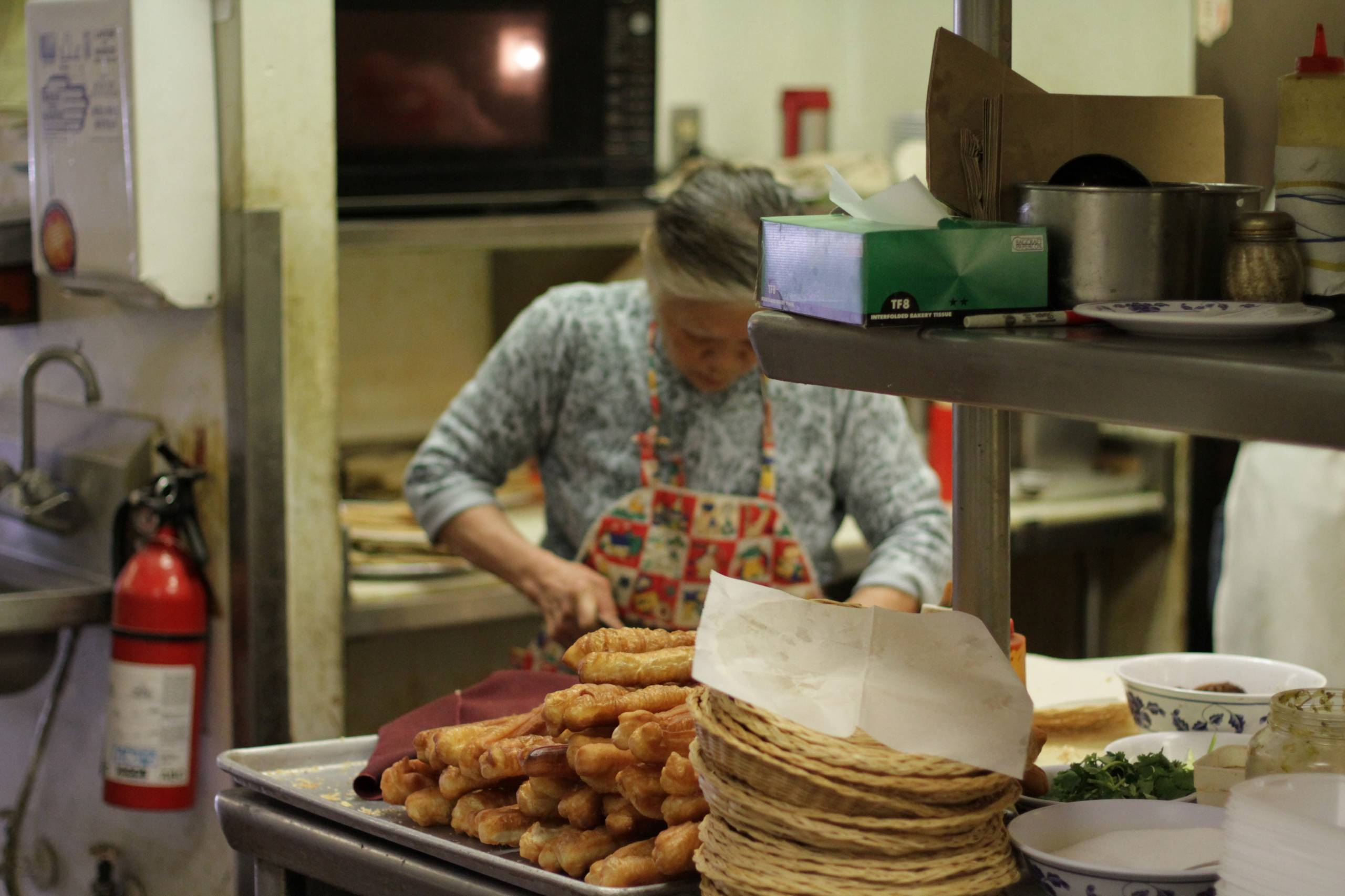 A woman preps the you tiao, or fried crullers, in the kitchen at Chef Wu