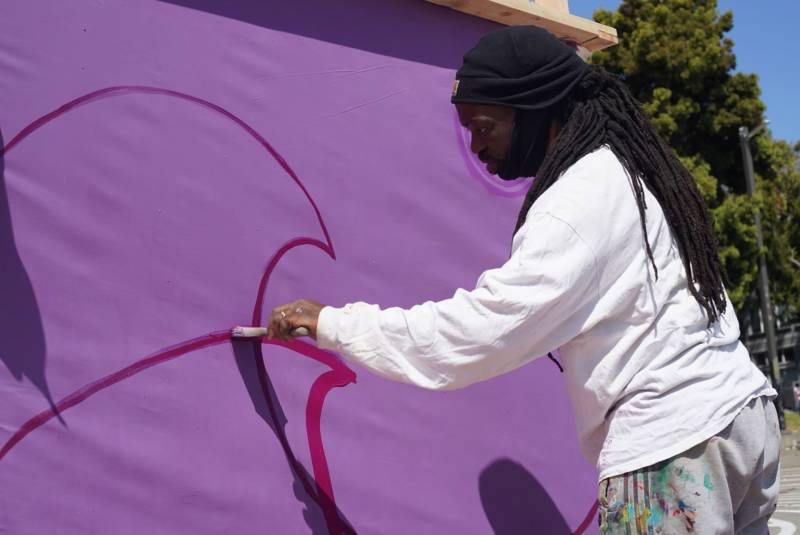 Malik Seneferu works on a mural in Oakland's Chinatown.