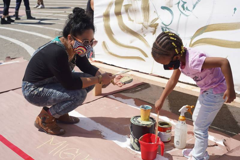 Cece Carpio, at left, collaborates with the author's daughter at an event prmoting Black and Asian solidarity in Oakland's Chinatown.