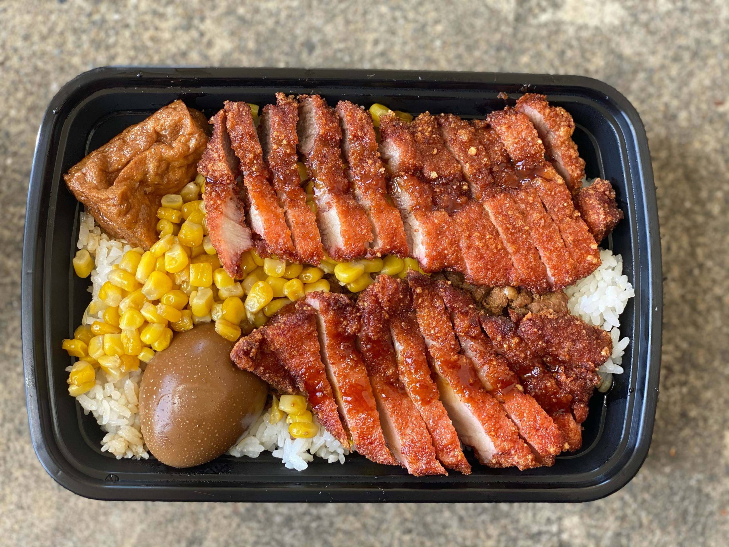 Overhead view of a red yeast pork bento box: slices of red-tinged crispy pork, corn kernels, a braised egg and tofu over white rice.