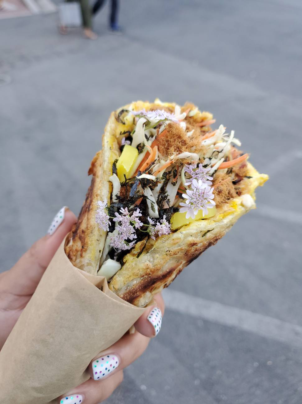 """A view of the """"Taiwan taco,"""" a scallion pancake stuffed with eggs, slaw, and edible flowers."""
