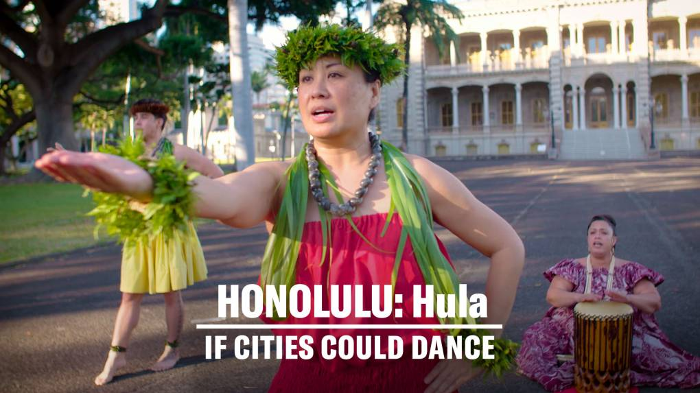 Female hula dancer in traditional attire extends her arm towards the camera.