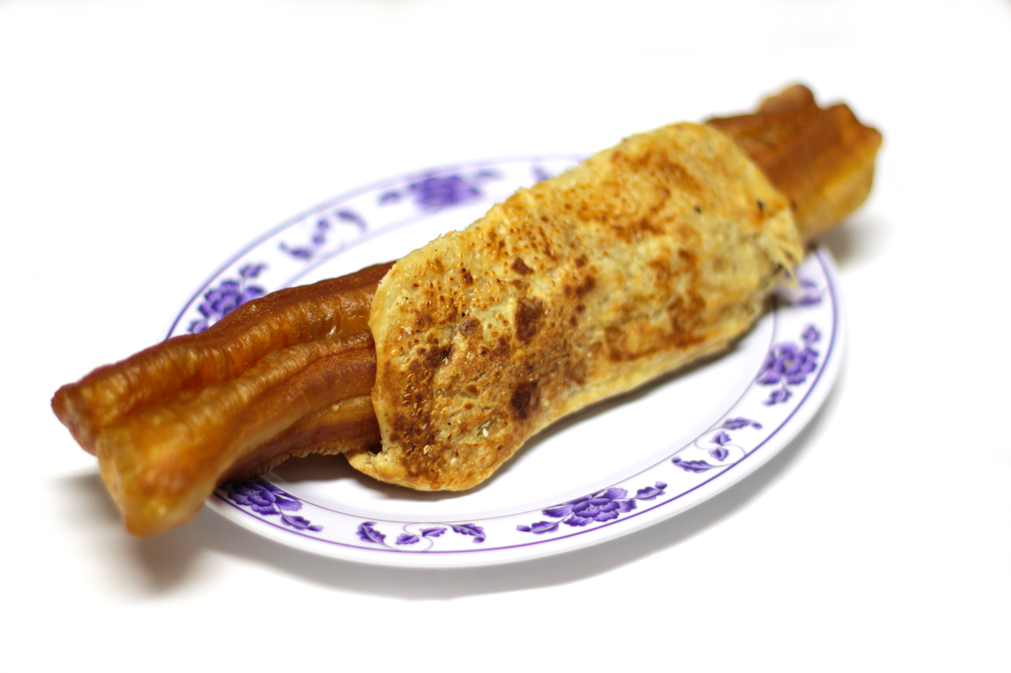 Shaobing you tiao (fried cruller wrapped in sesame flat bread) on a white ceramic plate against a white background.