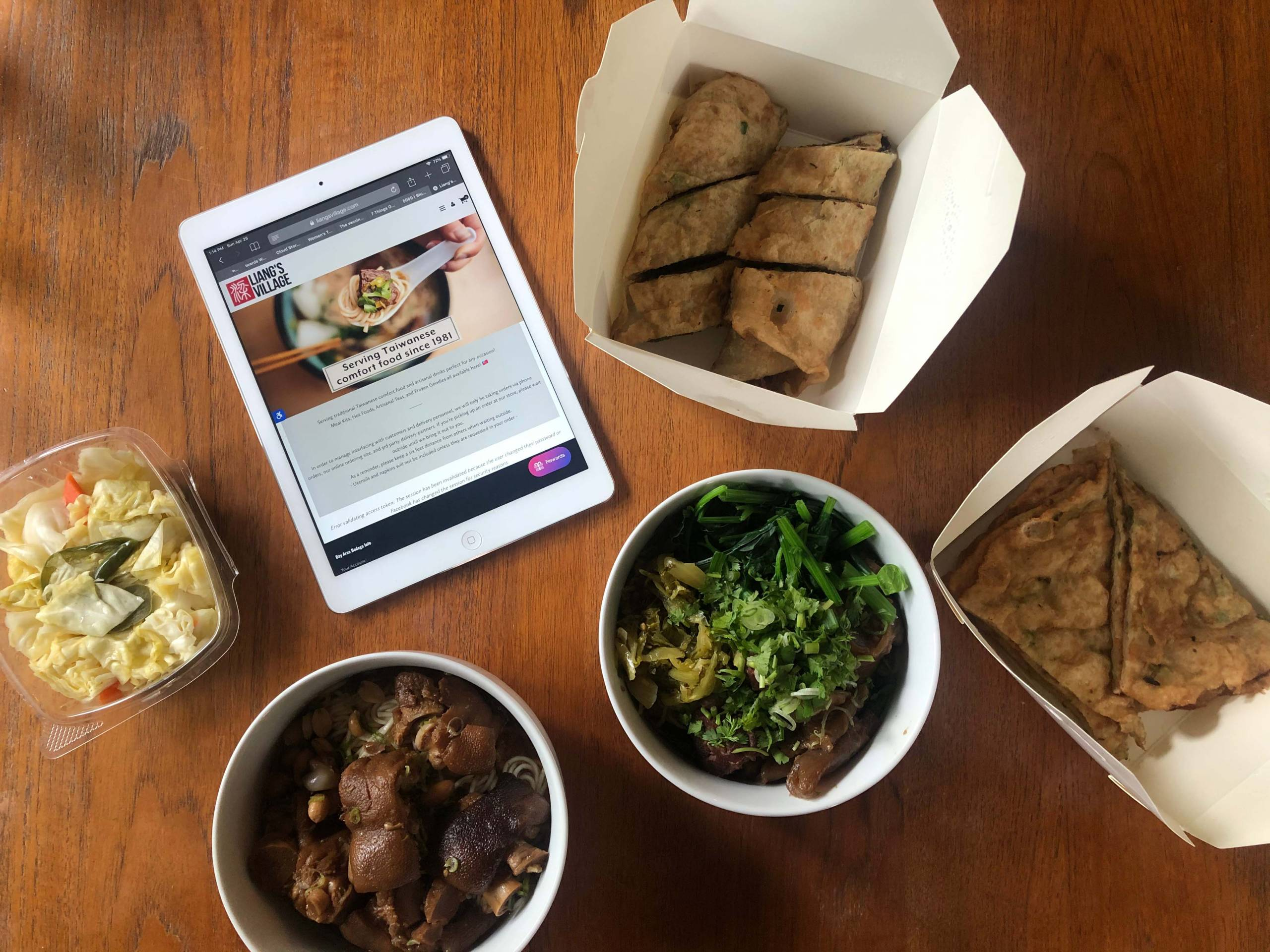A spread of takeout dishes from Liang's Village in white takeout cartons.