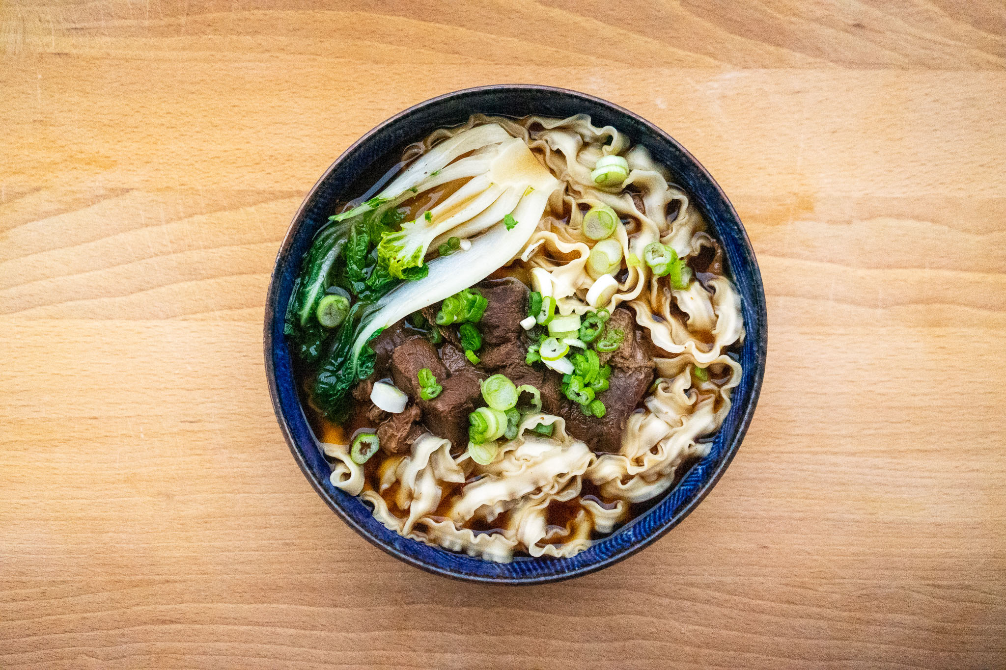 Overhead view of a bowl of beef noodle soup, garnished with bok choy and chopped scallions, on a wood table.