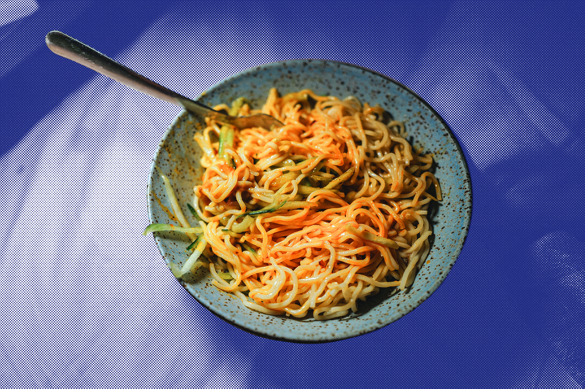 A bowl of Pintung cold noodles with peanut sauce, garnished with slivers of cucumber, against a blue backdrop.