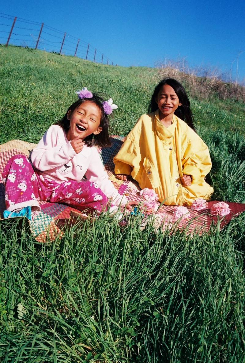 Been Milky's daughters smile and pose for a photo on a grassy hillside.