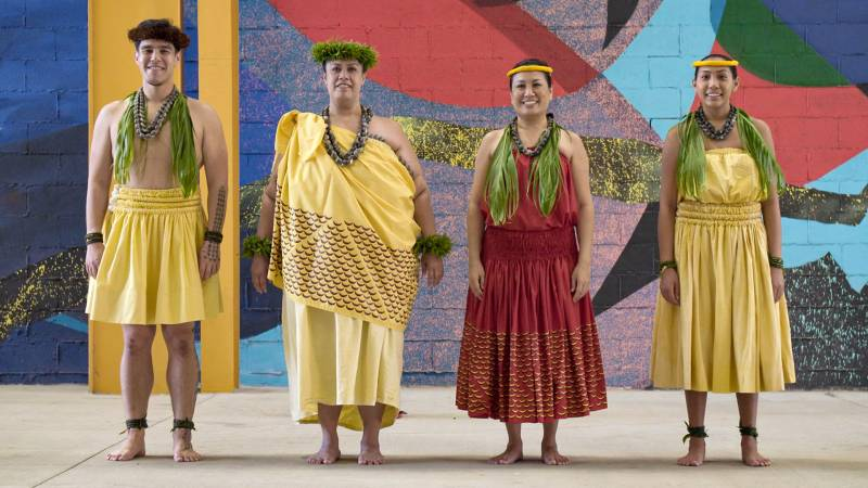 Four hula dancers in traditional attire pose in front of a colorful mural.