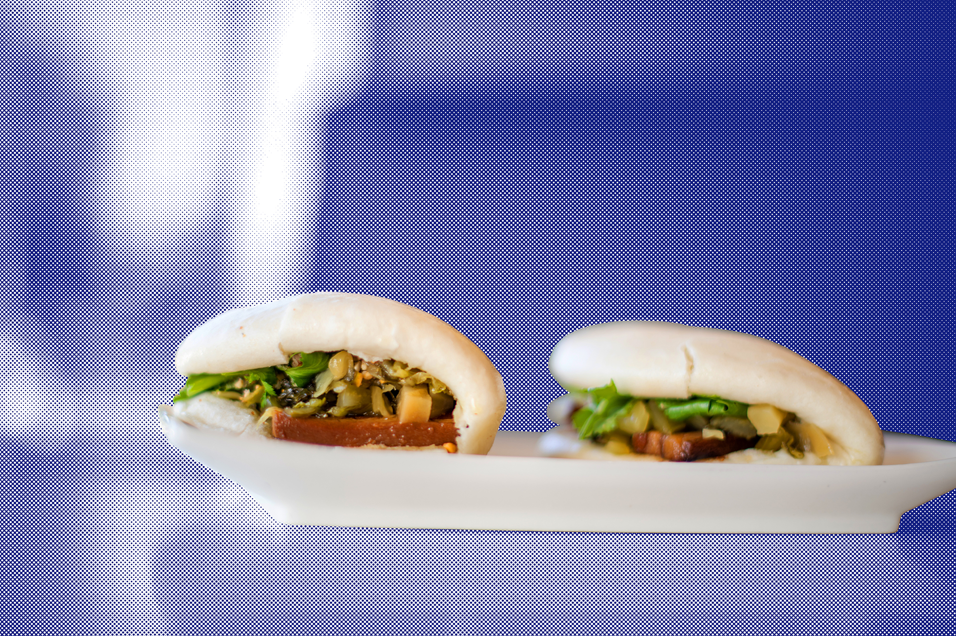 A pair of gua bao, or Taiwanese pork belly buns, on a white plate, against a stylized blue backdrop.