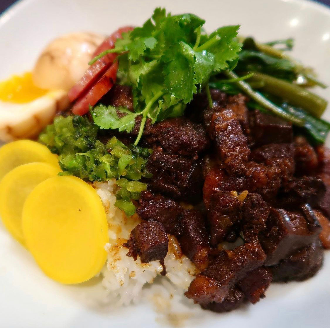 A bowl of lu rou fan, or braised pork rice, garnished with cilantro and yellow daikon pickles.