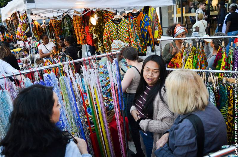 Women look at clothing in a festival booth filled with African fabrics.
