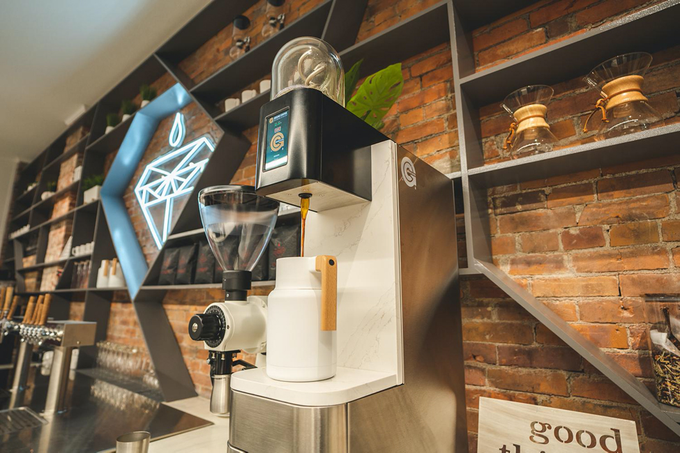 A Ground Control Coffee batch brewer in a coffee shop in front of an exposed brick wall with shelving.