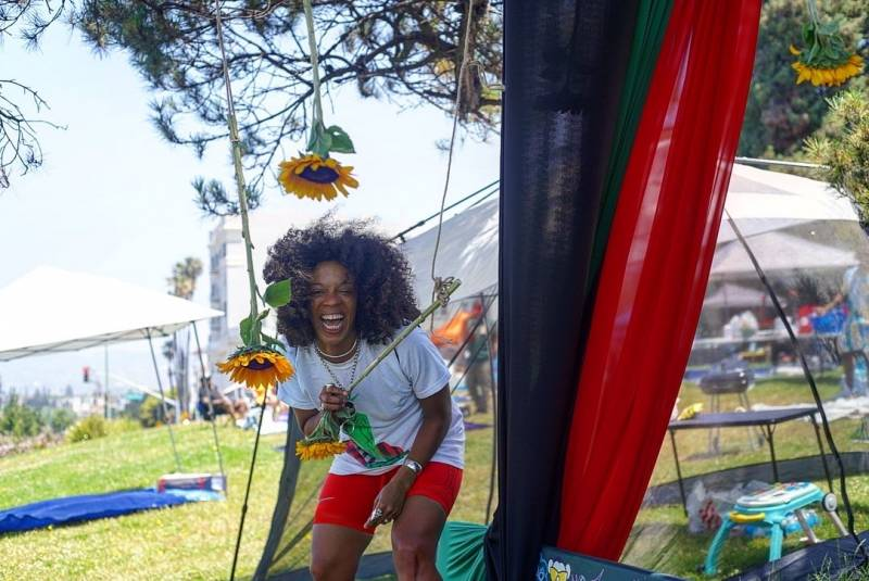 Zakiya smiles as she adorns a tree with sunflowers and a red, black and green cloth, as a part of a photo booth installation
